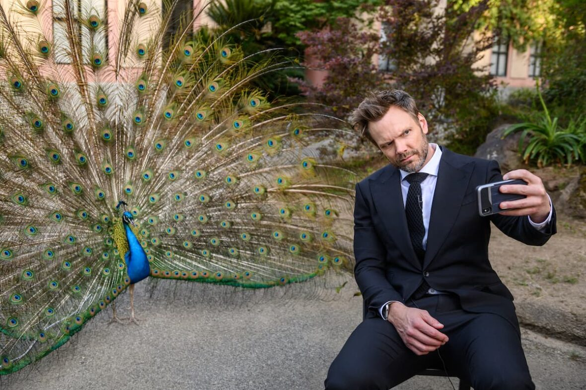 Joel McHale looking tough and taking a selfie in front of Kevin the peacock